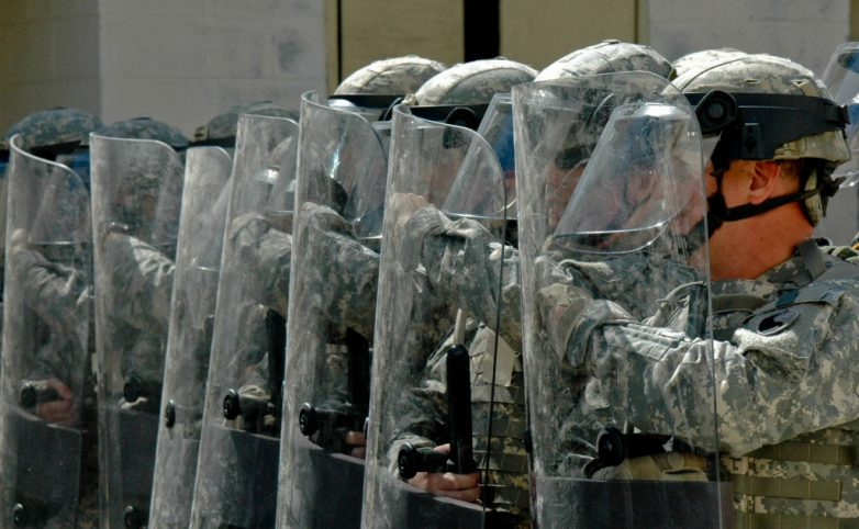 image of National Guard members lined up with riot shields, about to suppress free speech rights - Image is in the public domain, see https://vaguard.dodlive.mil/2012/04/15/930/